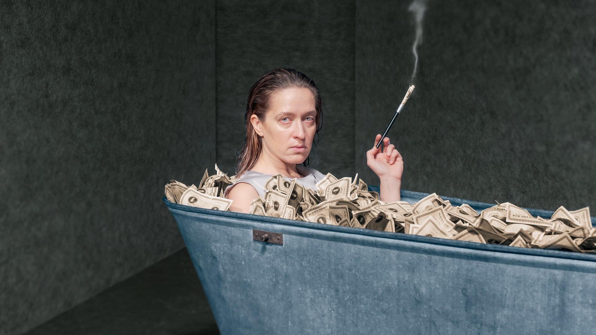 Elsa Saisio rahantäyteisessä kylpyammeessa