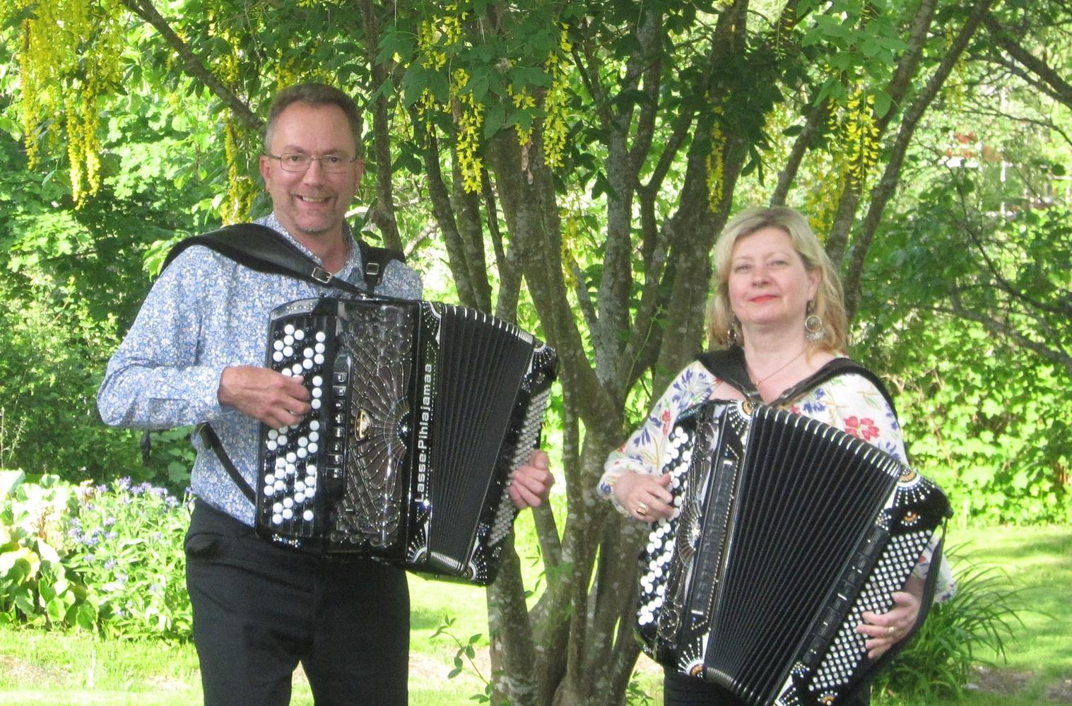 Pekka Pentikäinen ja Maria Kalaniemi soittavat harmonikkaa puun alla. Dragspelarna Pekka Petikäinen och Maria Kalaniemi under ett träd.
