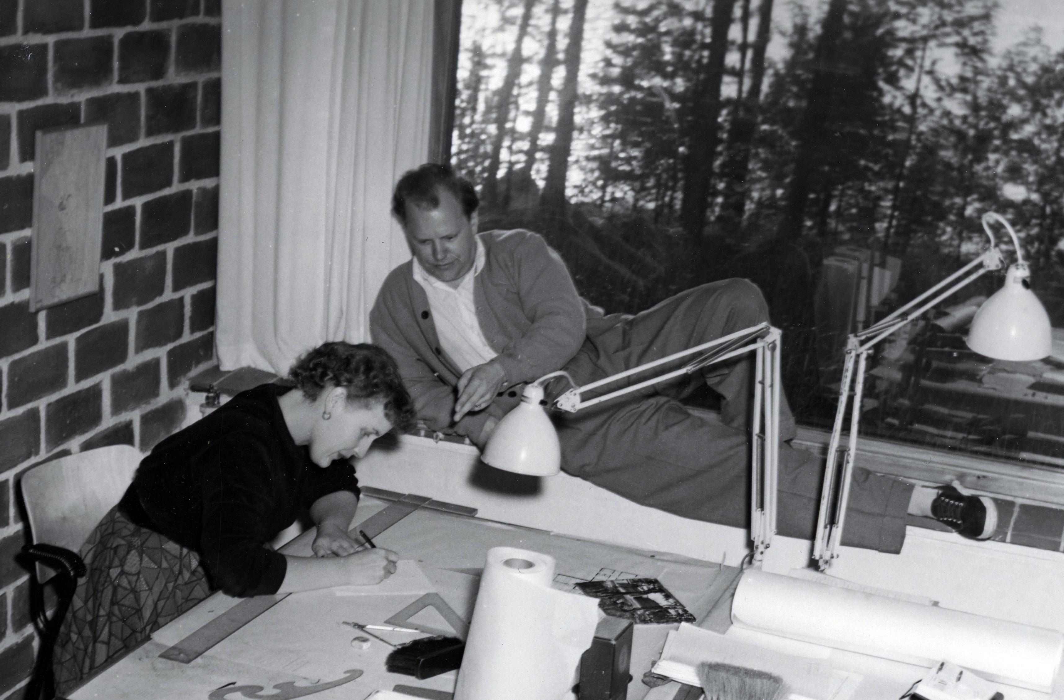Kaija ja Heikki Siren työskentelemässä toimistollaan. Heikki on kyljellään ikkunalaudalla, Kaija piirtää.
