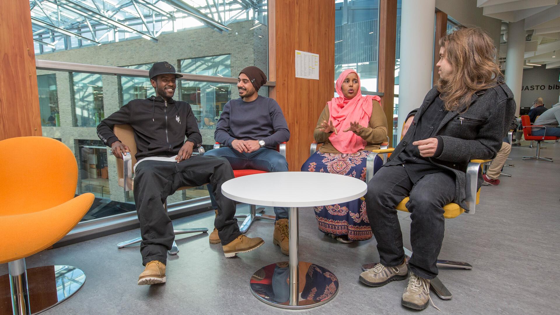 Valokuvassa neljä henkilöä keskustelee kirjastossa.